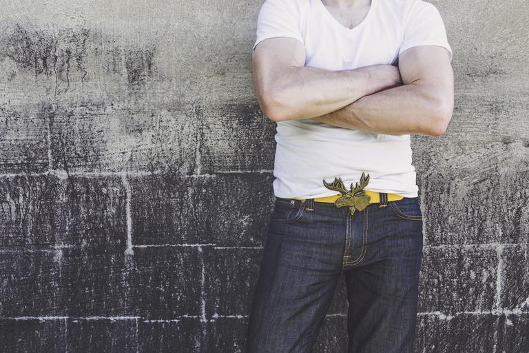 Muž v bielom tričku, džínsoch a opaskom v tvare jeleňa.jpg