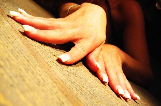 Ženské ruky s dlhými bielymi nechtami na podlahe