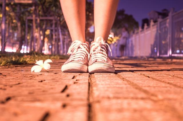 Žena v ružových teniskách stojí na chodníku vedľa kovového plotu