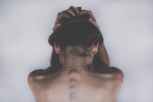 Žena s nahým chrbtom sa drží za vlasy