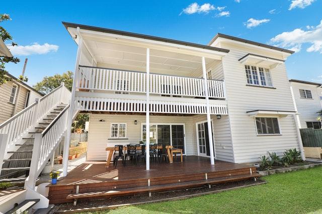Biely rodinný dom so schodiskom a zastrešeným balkónom.jpg