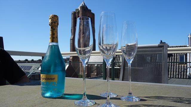 Šampanské a poháre na stopke, položené na stole na terase so skleneným zábradlím.jpg