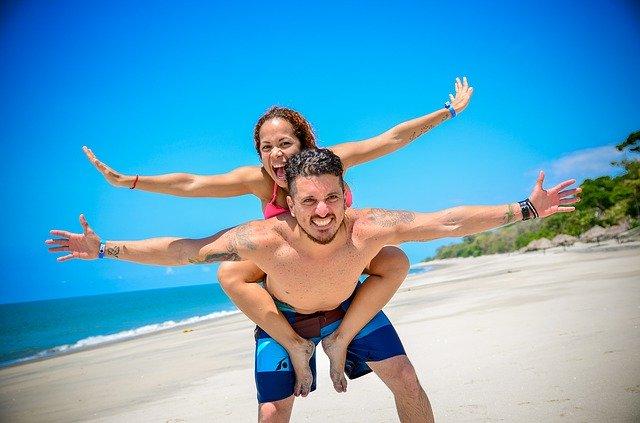 Muž nesie ženu na pleciach, pláž.jpg