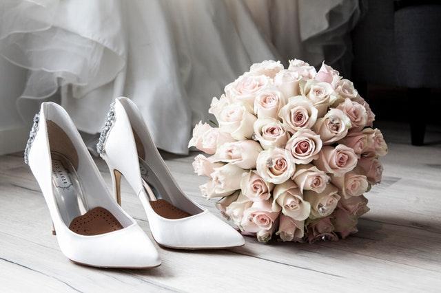 Biele svadobné topánky a svadobná kytica z ružových ruží.jpg