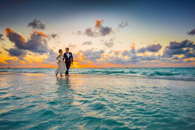 Žena v svadobných šatách a muž v smokingu kráčajú po pláži.jpg